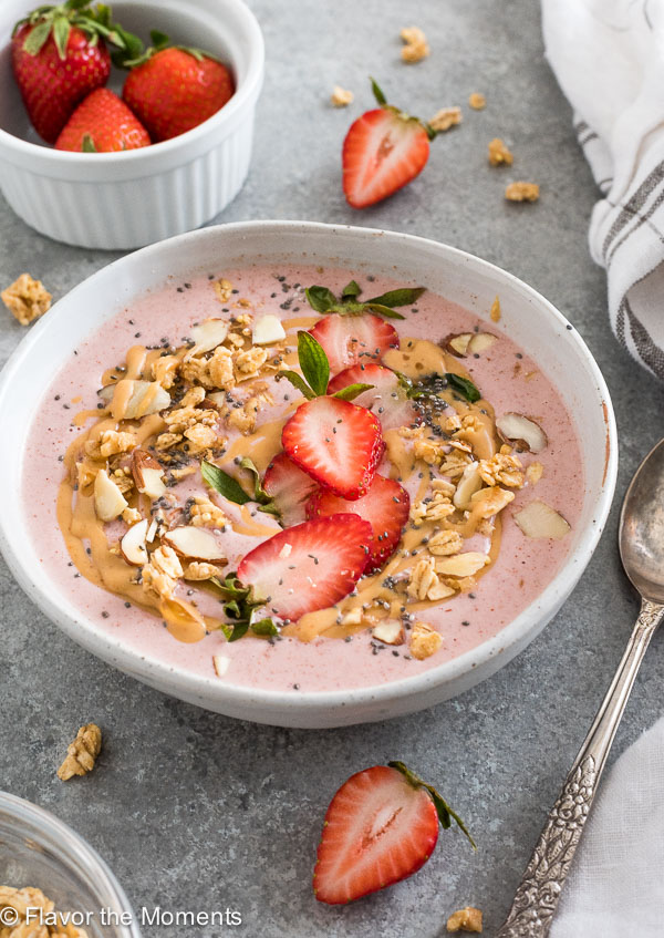 Strawberry smoothie bowl in white bowl with granola and fruit on top