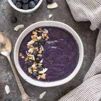 Blueberry banana smoothie bowl in white bowl with granola and berries on top