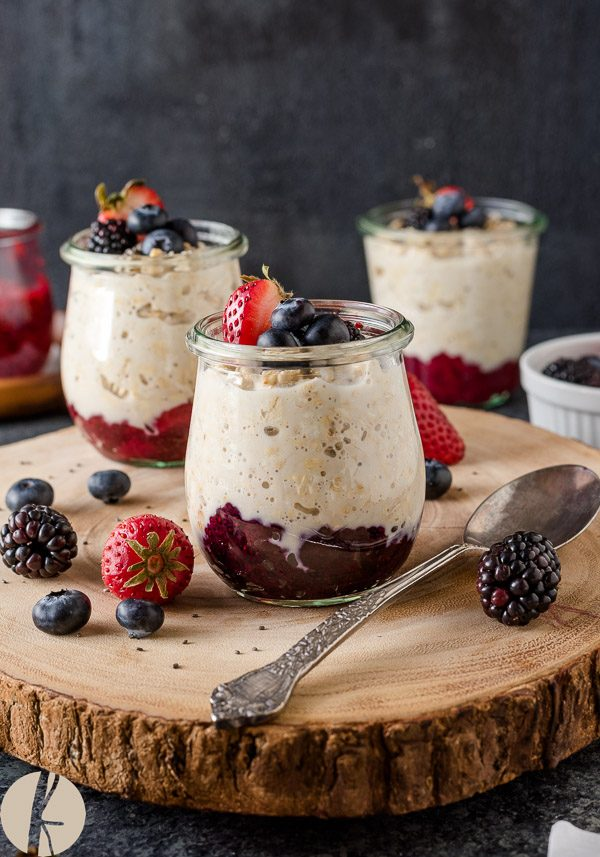 Chia jam overnight oats in jars on a server with berries on top