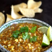 Tomatillo corn salsa in blue and white bowl with chips