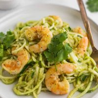 Tomatillo salsa shrimp zoodles on a white plate with a fork.