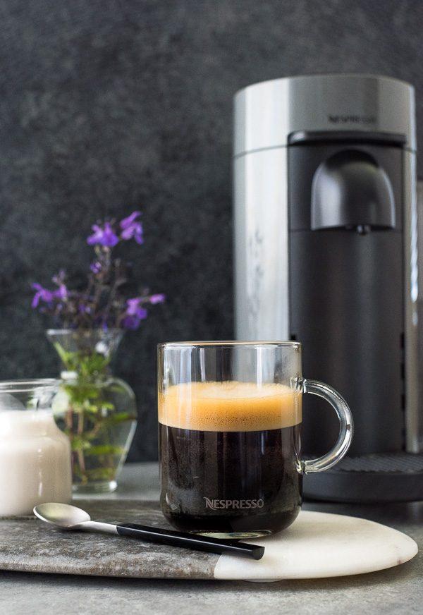 Nespresso Vertuoplus Machine in background with Americano coffee