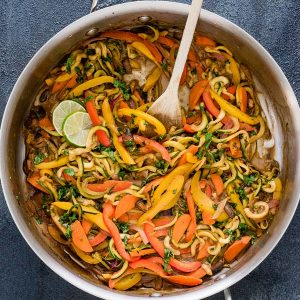 Vegetarian thai peanut zucchini noodles in a skillet with wooden spoon