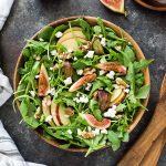 Apple fig arugula salad in a bowl with servers