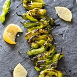 Grilled shishito peppers on serving board with lemon and sea salt