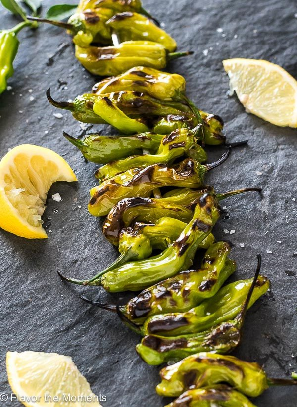 Close up of grilled shishito peppers lined up on board with lemon