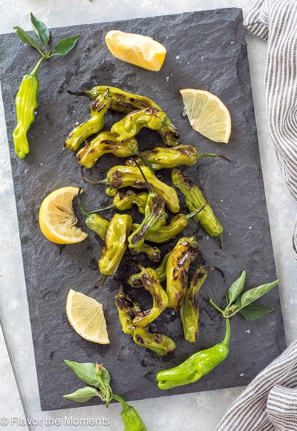 Grilled shishito peppers scattered on serving board with lemon