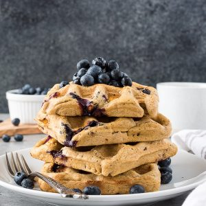 Stack of oat flour waffles on a plate with blueberries on top