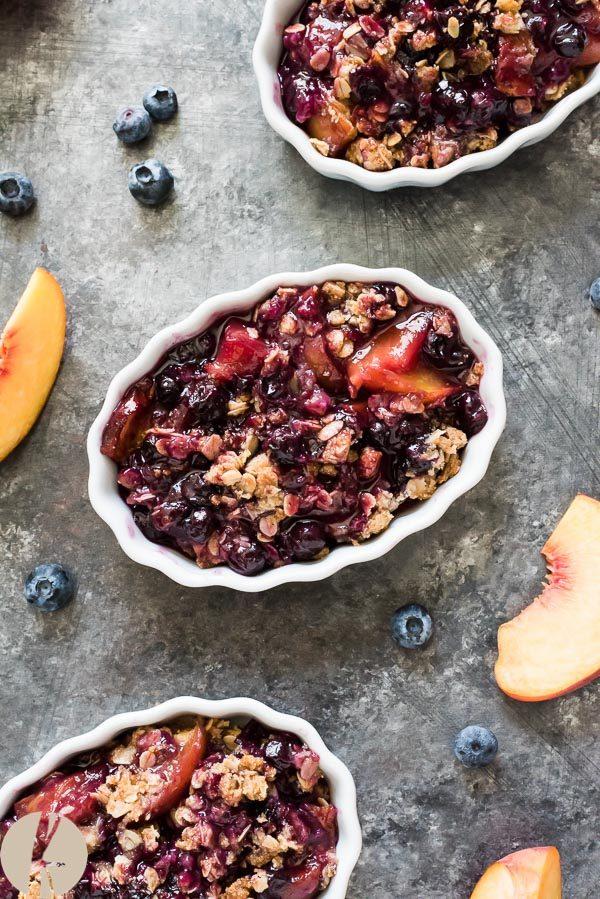 serving of peach blueberry crisp in ramekin with fruit around it