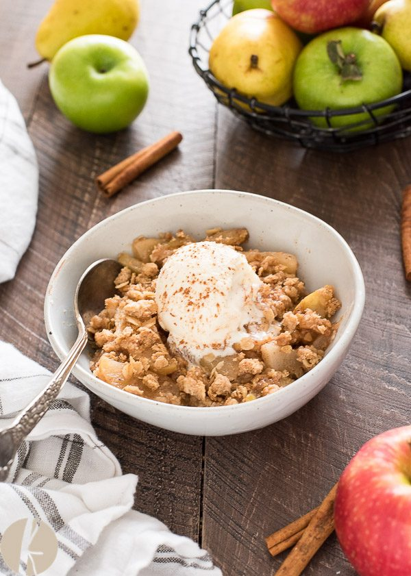 Apple pear crisp in white bowl with ice cream on top