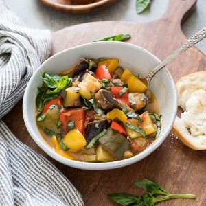 bowl of instant pot ratatouille with spoon in the bowl and bread alongside
