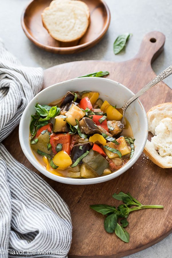 Bowl of Instant Pot ratatouille with spoon buried inside and bread