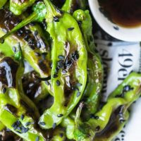 Grilled shishito peppers topped with black sesame seeds.