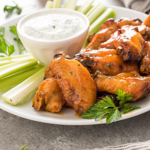 White plate with Instant Pot chicken wings, celery and ranch dressing