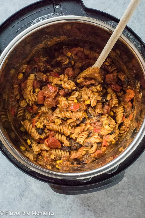 instant pot pumpkin chili mac in Instant Pot with wooden spoon