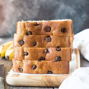 Gluten free banana bread stacked on wooden board with chocolate chips