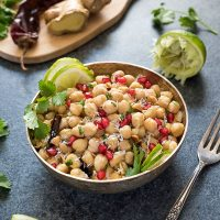 Chickpea salad in silver bowl with lime, cilantro and pomegranate