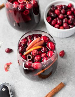 Glass of cranberry sangria with fresh cranberries, apples and cinnamon