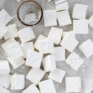 Homemade marshmallows on parchment paper with sieve and powdered sugar
