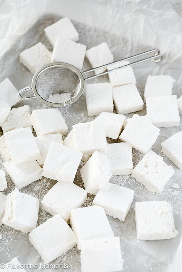 Marshmallows piled on parchment lined baking sheet