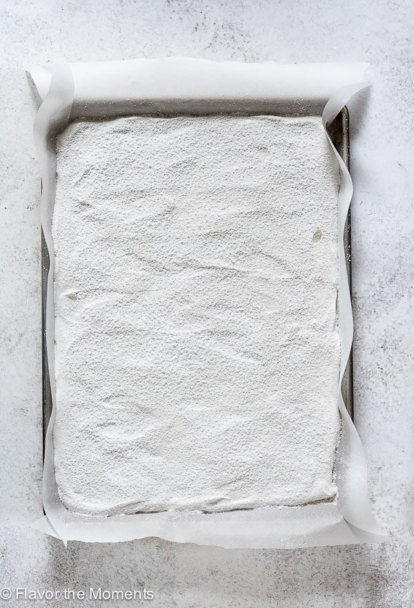 Marshmallows spread on a parchment lined baking sheet