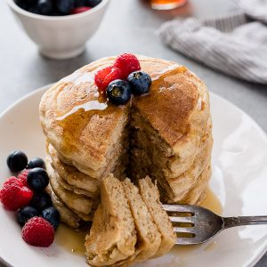 Stack of Greek yogurt pancakes on a plate with berries on top and bite removed