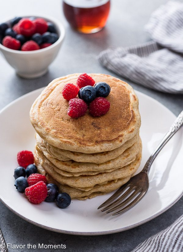 Stack of Greek yogurt pancakes on a plate with berries on top