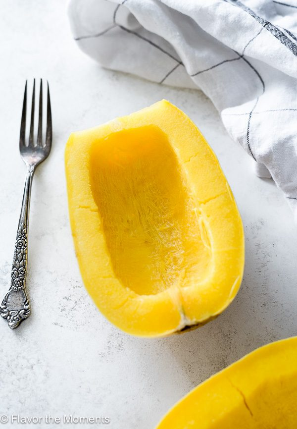 Cooked spaghetti squash cut in half with fork alongside