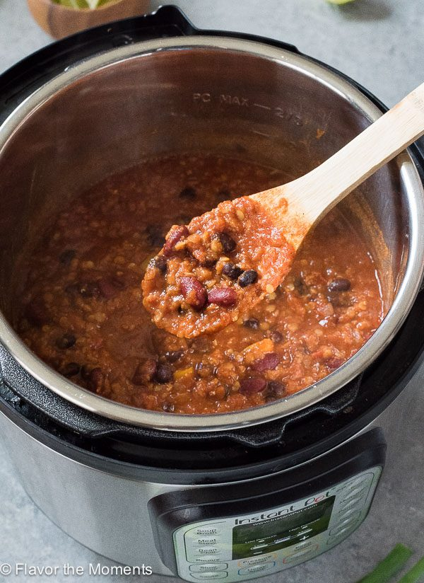 Wooden spoon with taco lentil chili over instant pot