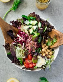 Italian chopped salad in white bowl with wooden servers