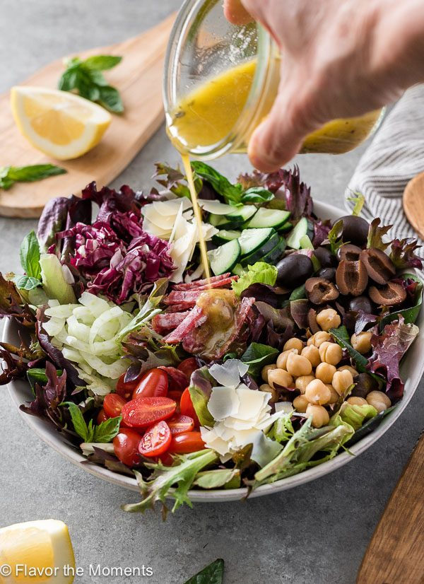 Italian chopped salad with dressing pouring over the top