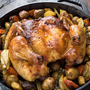 Spatchcock roast chicken in skillet with potatoes, fennel and carrots