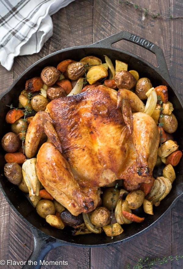 Overhead of roasted spatchcock chicken in skillet with potatoes, fennel and carrots
