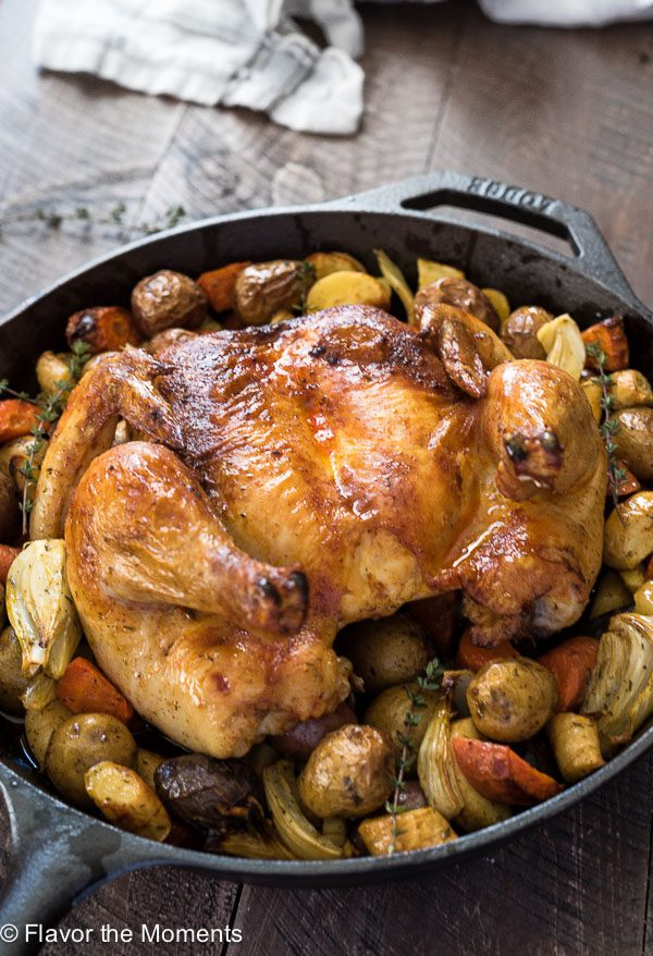 Spatchcock chicken in skillet with vegetables