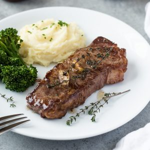 Pan seared steak on plate with broccoli and mashed potatoes