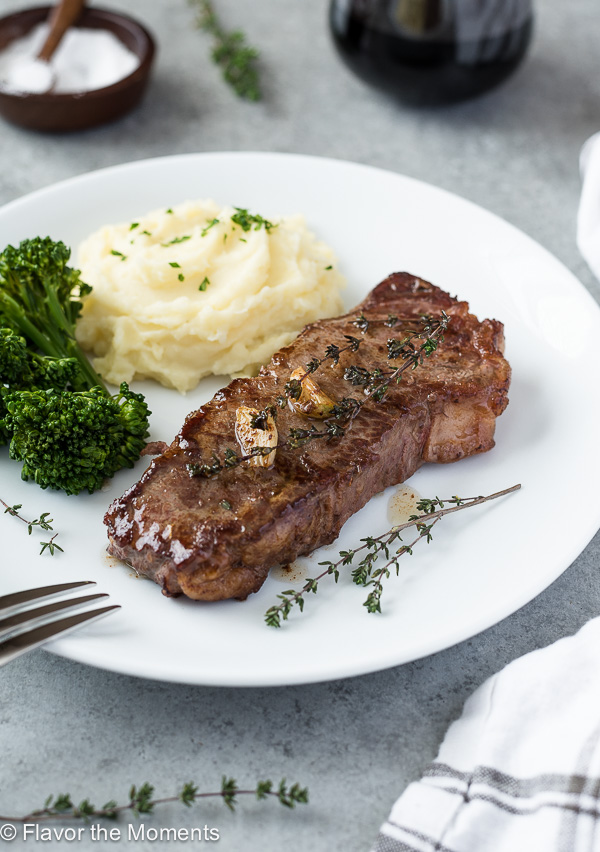 Pan seared steak on plate with mashed potatoes and broccoli