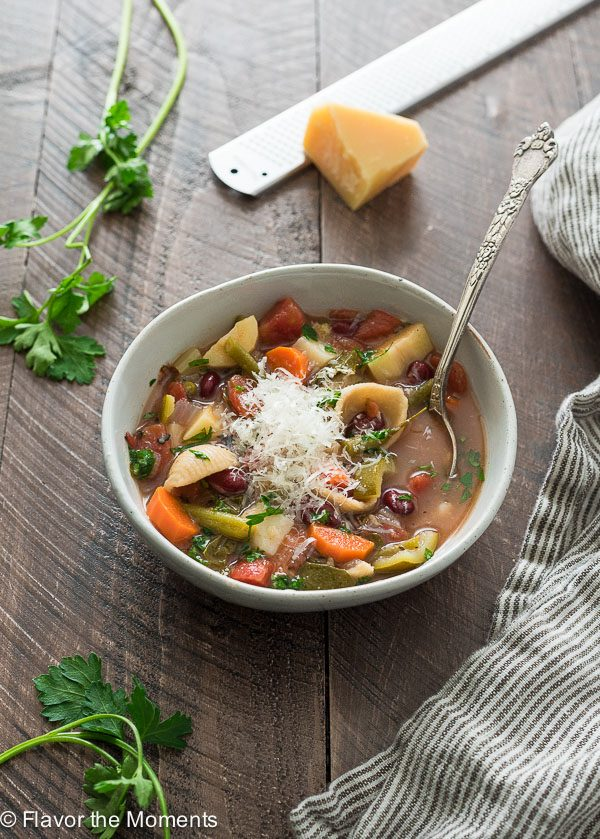 Bowl of Instant pot vegetarian minestrone soup with spoon and parmesan