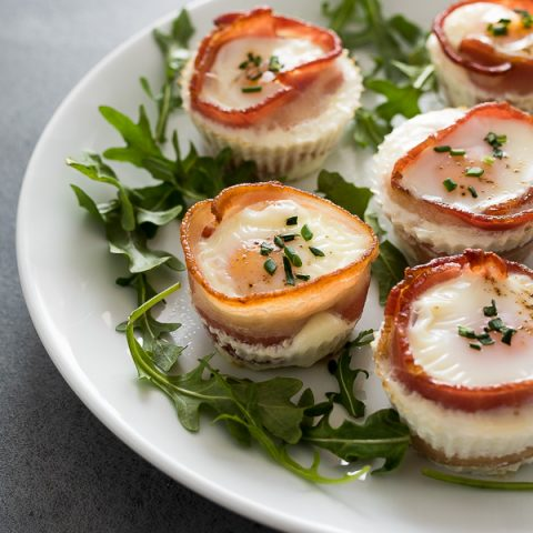 Bacon egg cups on a white plate with arugula