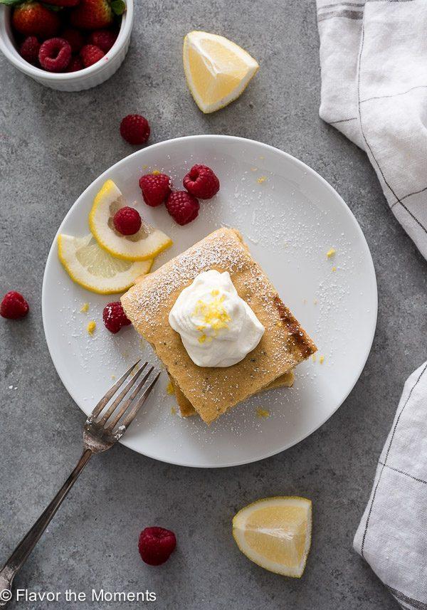 White plate with sheet pan pancakes, lemon and raspberries