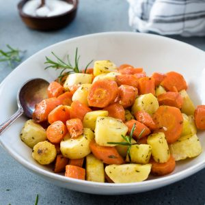 Roasted carrots and parsnips in a white bowl with spoon