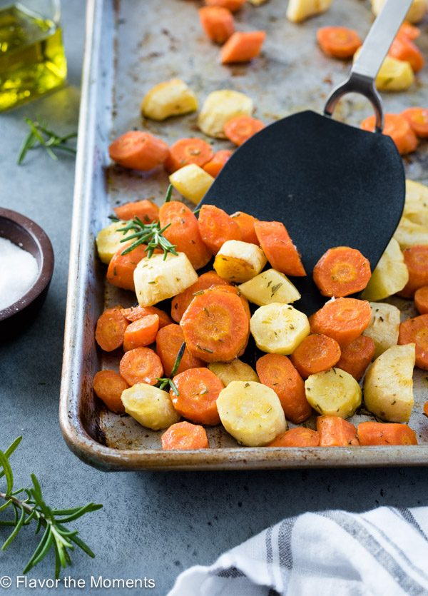 Roasted carrots and parsnips on baking sheet with spatula