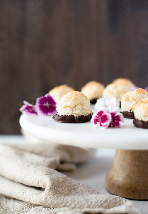 chocolate dipped coconut macaroons on pedestal with edible flowers front view