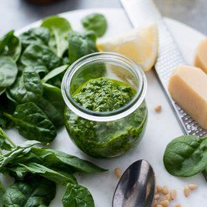Pesto sauce in jar with greens, lemon and parmesan
