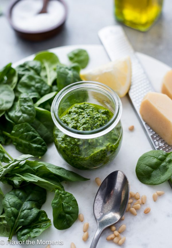 Pesto sauce in jar with greens and parmesan alongside