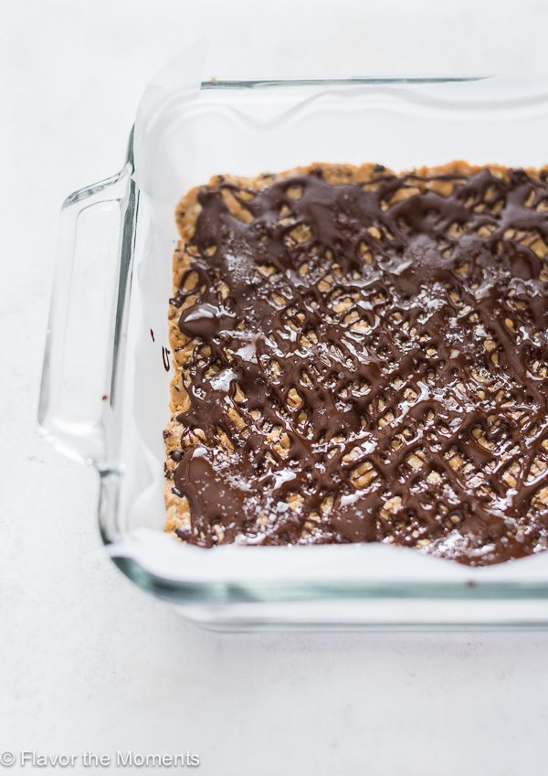 no bake peanut butter oatmeal bars in pan after drizzling with chocolate