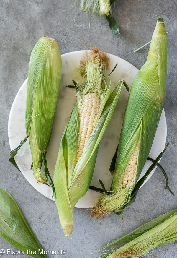 overhead shot of corn on the cob on round white marble board