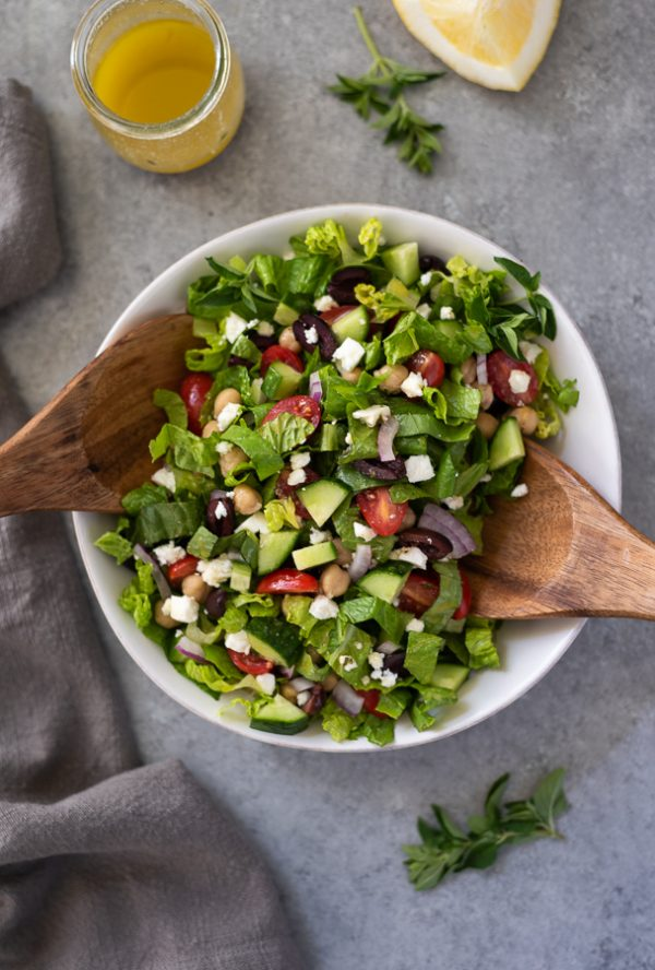 Greek chopped salad in white bowl with teak servers