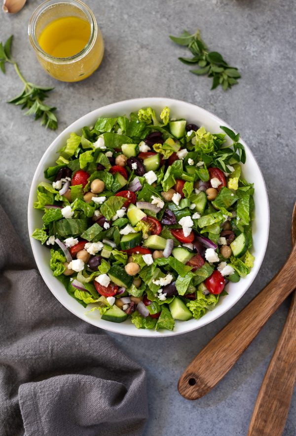 overhead shot of Greek chopped salad with linen and wooden spoons alongside