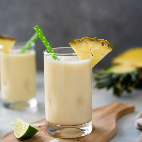 Pina colada smoothie in glasses with pineapple slice and green straw