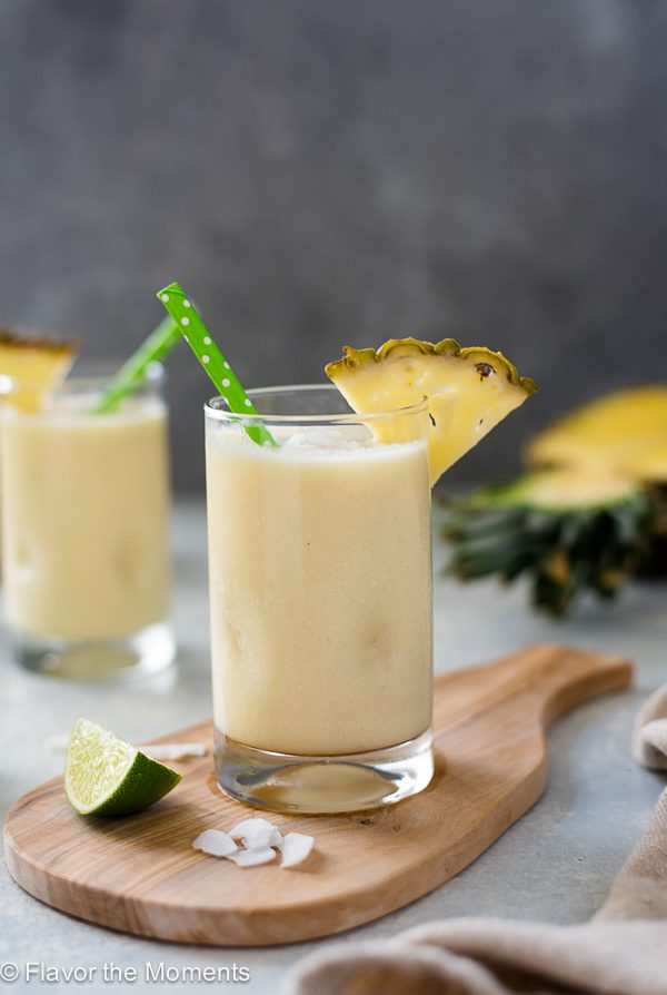 Pina colada smoothie on wooden board with pineapple slice and lime